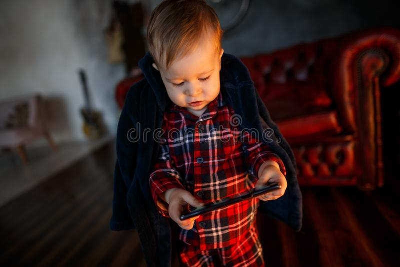 小婴孩是站立和拿着片剂在手上 他看它 集中孩子 免版税库存图片