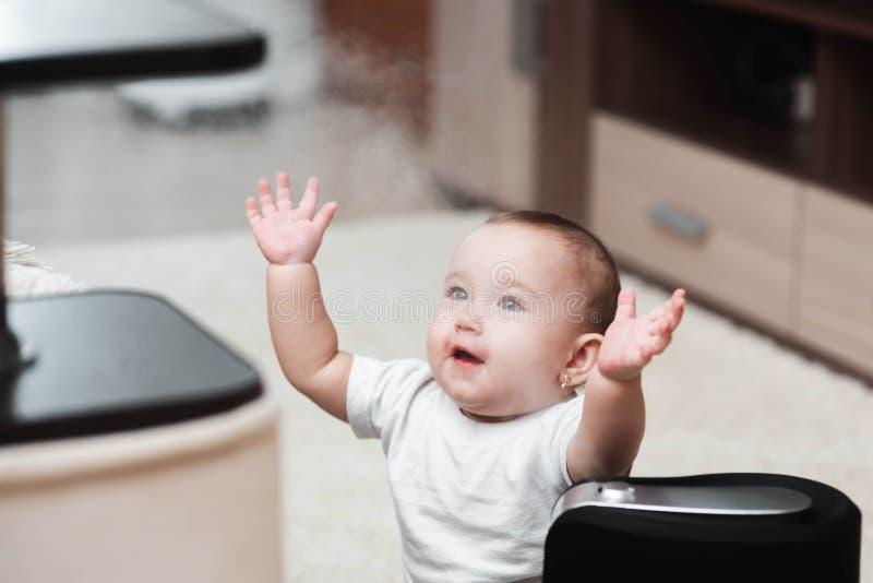 小婴孩看润湿器 在房子概念的湿气 库存图片