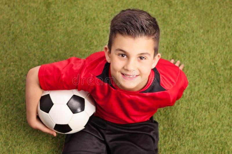 小字辈橄榄球球员坐草和微笑 图库摄影