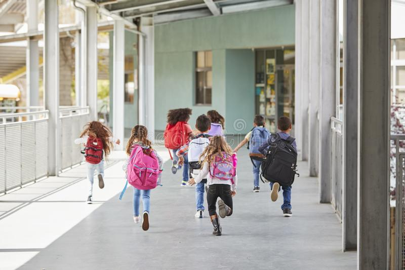 小学孩子从在学校走廊的照相机跑 库存照片