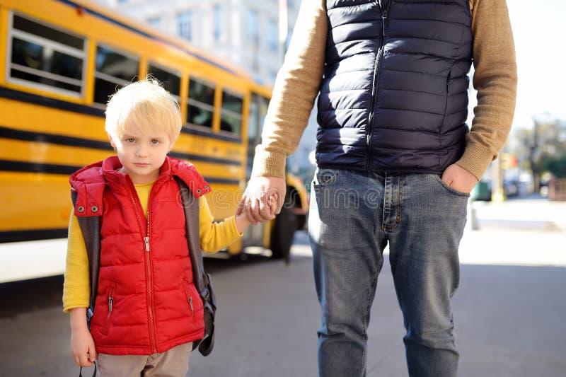 小学生举行手他的在黄色学校班车附近的父亲在背景 图库摄影