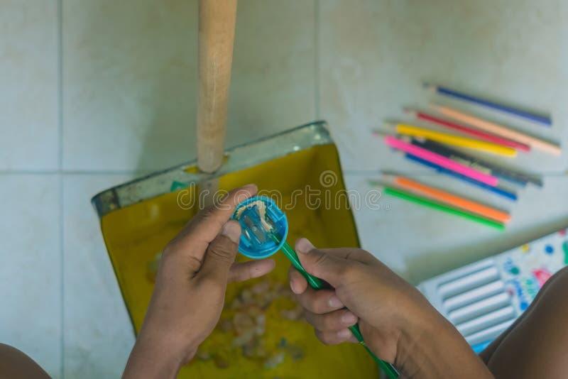 小学生削尖颜色铅笔入簸箕 库存图片