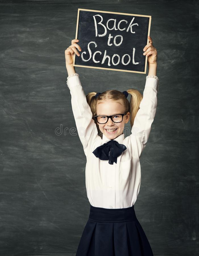 小学生有白垩凹道的藏品黑板,回到学校,在黑背景,给女孩做广告 免版税库存图片