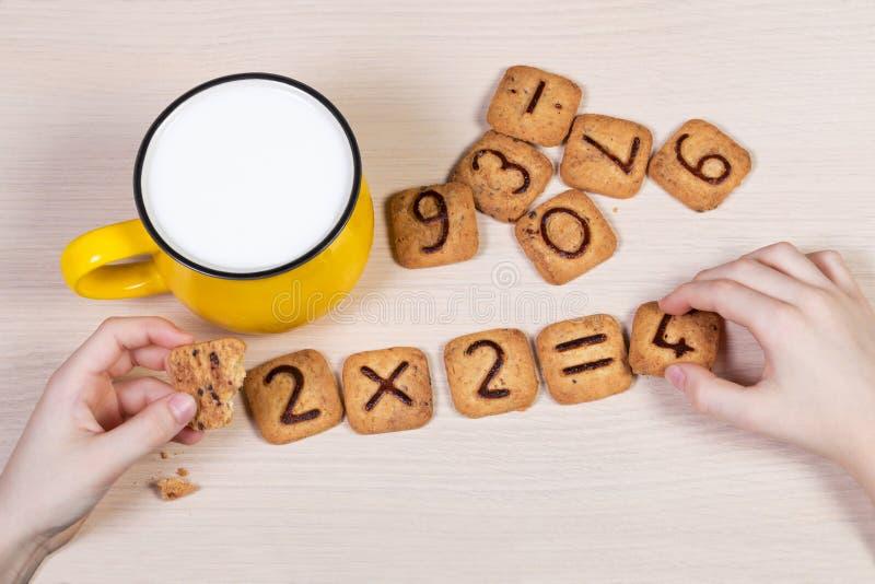 小学生的健康早餐 挤奶在明亮的黄色杯子和滑稽的曲奇饼与数字 免版税图库摄影