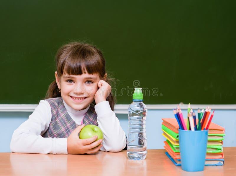 小学的一位愉快的女小学生的画象在黑板附近的 库存图片