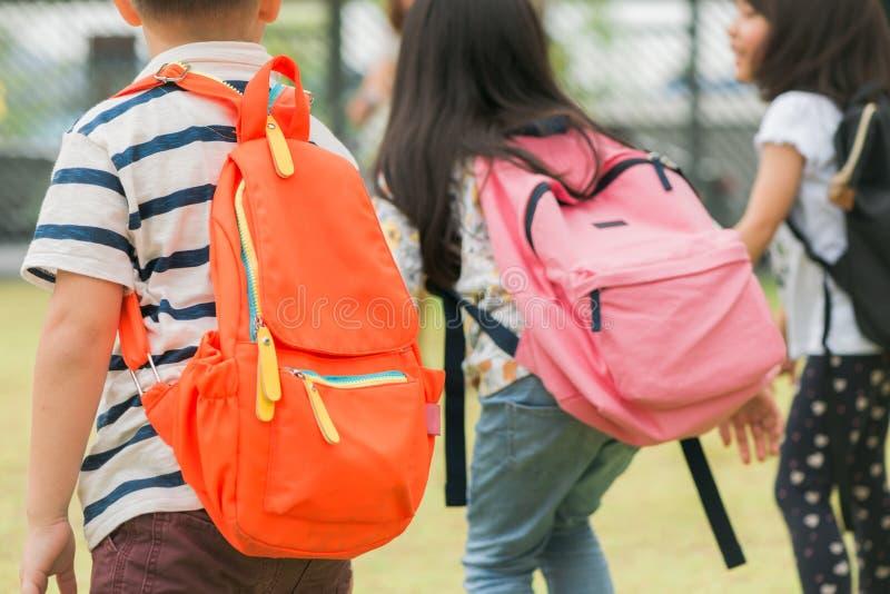 小学的三个学生联合发生 男孩和女孩有书包的在后面后 学校教训起点  免版税库存照片