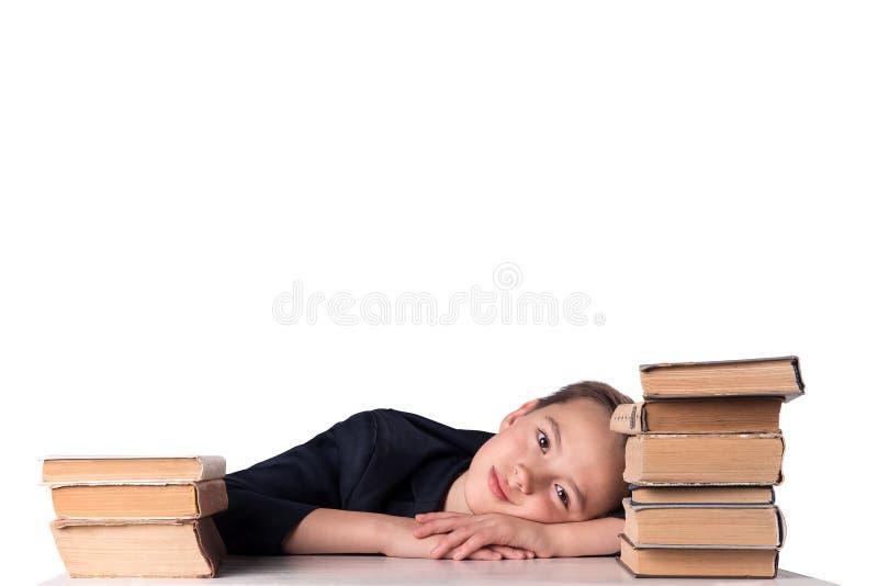小学年龄的孩子做家庭作业 男孩在家做他的家庭作业在他的书桌 免版税库存照片