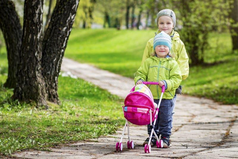 小孩、兄弟和姐妹在有玩具婴儿车的围场使用 使用在绿色公园的孩子在春天 免版税库存图片