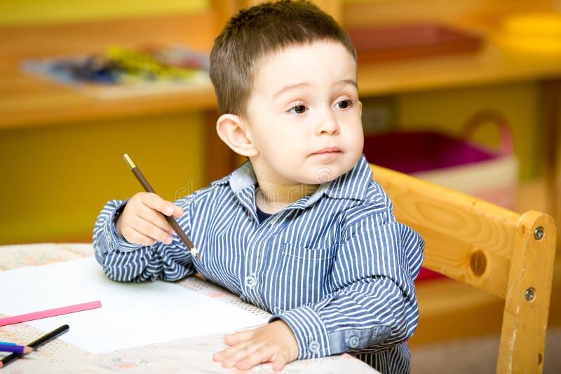 小孩与五颜六色的铅笔的男孩图画在幼儿园在桌上在幼儿园 免版税图库摄影