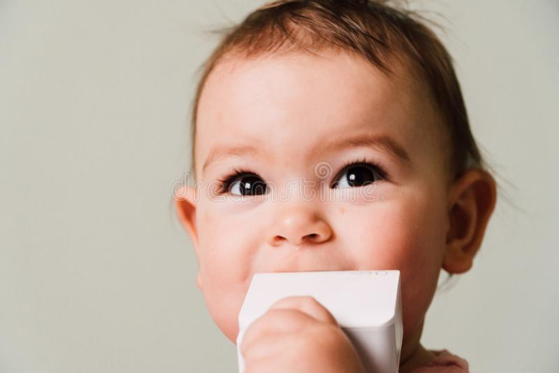 小孩与白色玩具的婴孩出牙,关闭童年画象  免版税库存图片