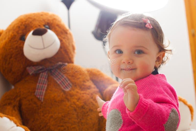 小孩使用与大玩具熊的女婴 库存照片