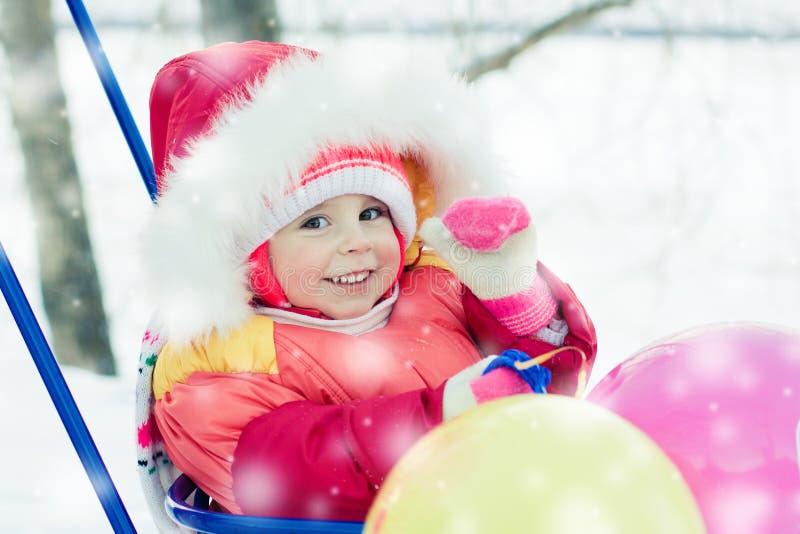 小孩冬天sledding与气球。 免版税库存照片