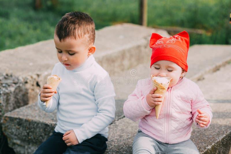 小孩吃冰淇淋的兄弟和姐妹户外 免版税库存图片