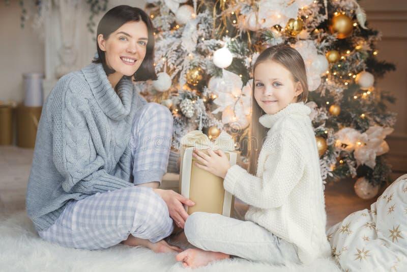小孩和她的母亲坐温暖的白色地毯近装饰的新年树,举行当前在手上,喜欢和愉快 免版税图库摄影