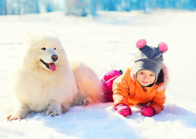 小孩和白色萨莫耶特人在雪冬日尾随说谎 图库摄影