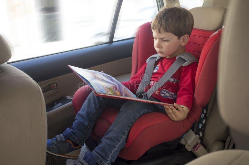 小孩在儿童汽车座椅的男孩看书 库存照片