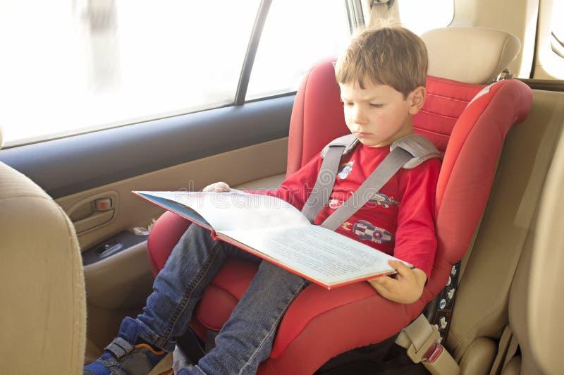 小孩在儿童汽车座椅的男孩看书 免版税图库摄影