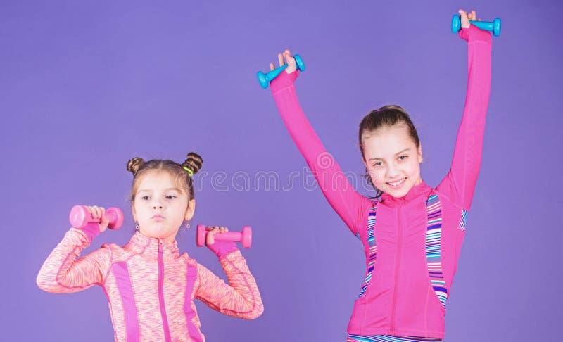 小孩在姐妹以后的重复锻炼 孩子的体育锻炼 健康养育 运动的婴孩 在她的姐妹之后 免版税图库摄影