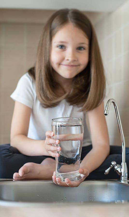 小孩在家喝着净水,关闭  有长发的白种人逗人喜爱的女孩在她的手上拿着一块水玻璃 免版税库存图片