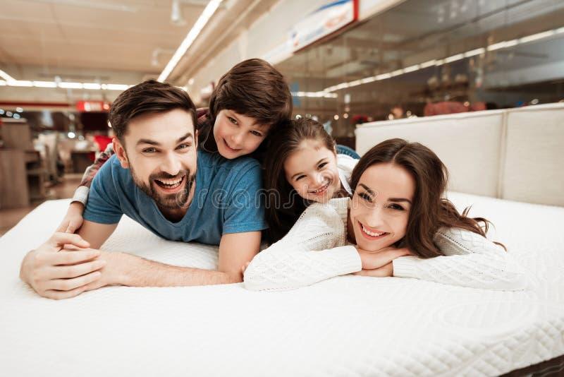 小孩在年轻愉快的父母后面说谎在床垫商店 免版税库存照片