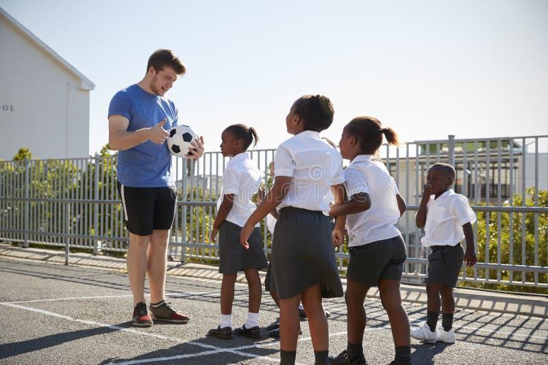 小孩在有拿着球的老师的一个学校操场 免版税库存图片