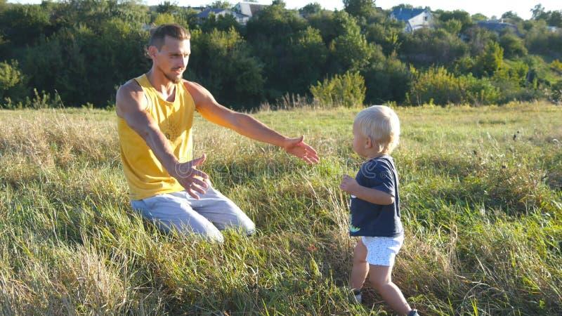 小孩在绿草去在领域他的父亲晴天 举他的男婴的爸爸在自然 愉快 免版税库存照片