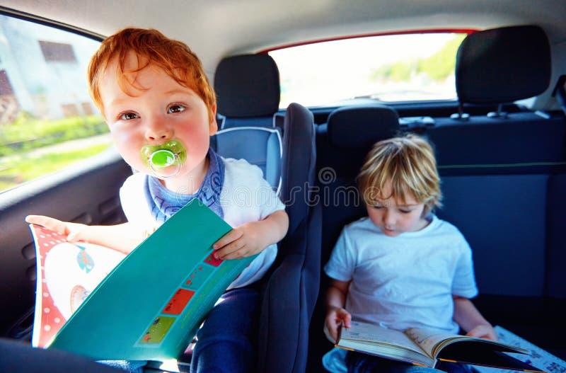 小孩坐后座,阅读书,当旅行在汽车时 免版税库存照片