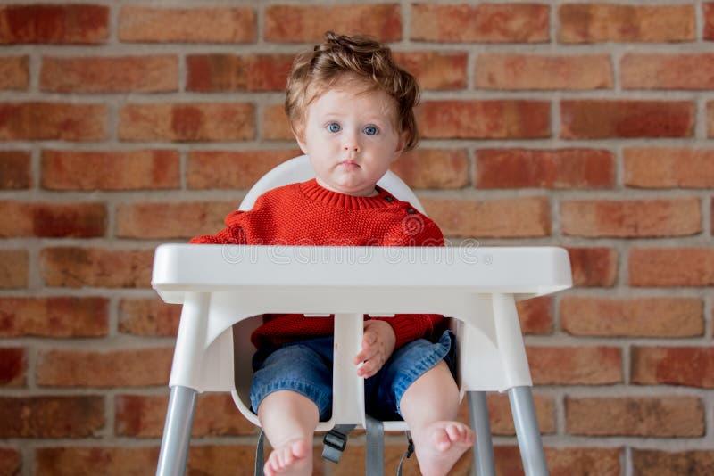 小孩坐在扶手椅子的男婴 库存照片