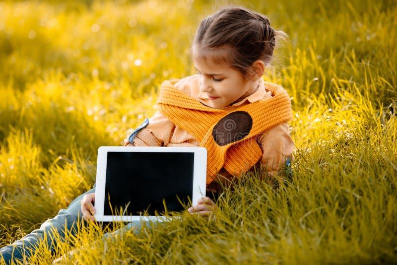 小孩坐秋天草和显示数字式 库存图片
