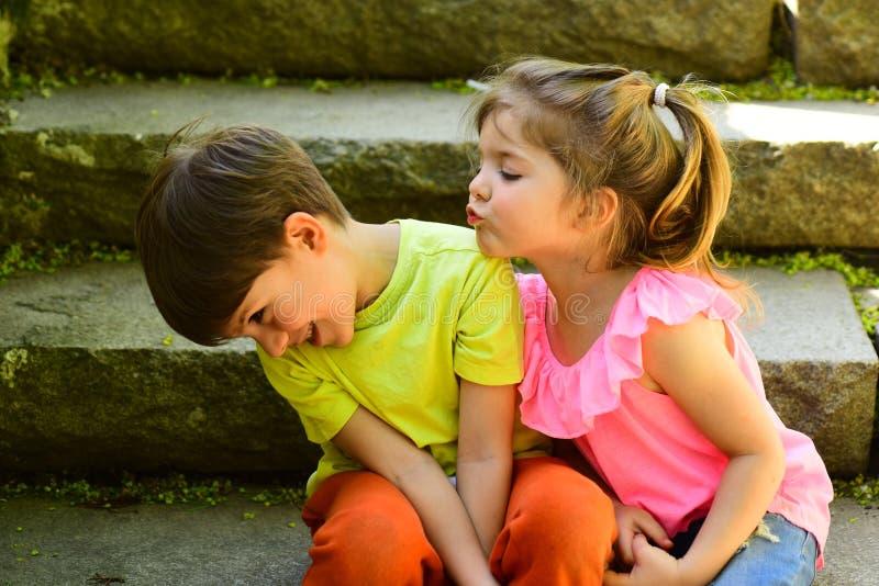 小孩夫妇  男孩和女孩 童年首先爱 小女孩和男孩台阶的 关系 使布赖顿椅子日甲板英国节假日懒人海边有风夏天的星期日靠岸 免版税库存图片