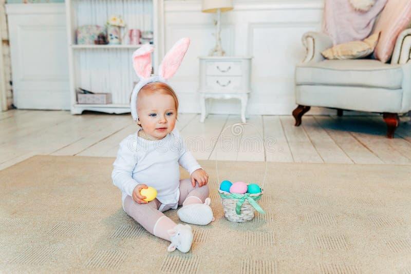 小孩女孩佩带的兔宝宝耳朵在复活节天和使用用被绘的鸡蛋 免版税库存照片