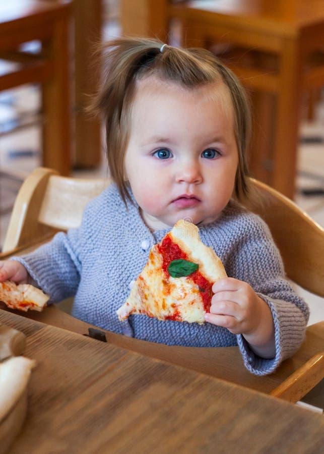 小孩女孩喜欢吃薄饼,垂直 免版税库存图片
