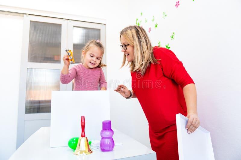 小孩女孩在儿童做与她的治疗师的作业治疗会议上知觉嬉戏的锻炼 免版税库存图片