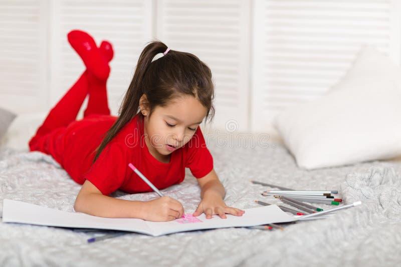 小孩女孩在家画与铅笔 免版税库存照片