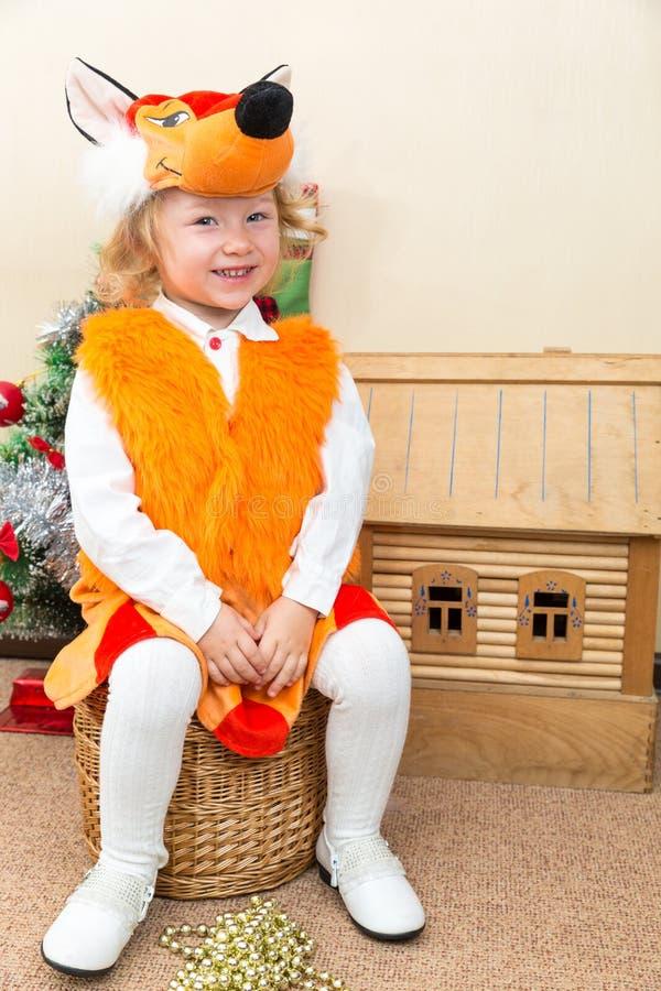 小孩女孩在狐狸衣服穿戴了在圣诞树附近 免版税库存图片