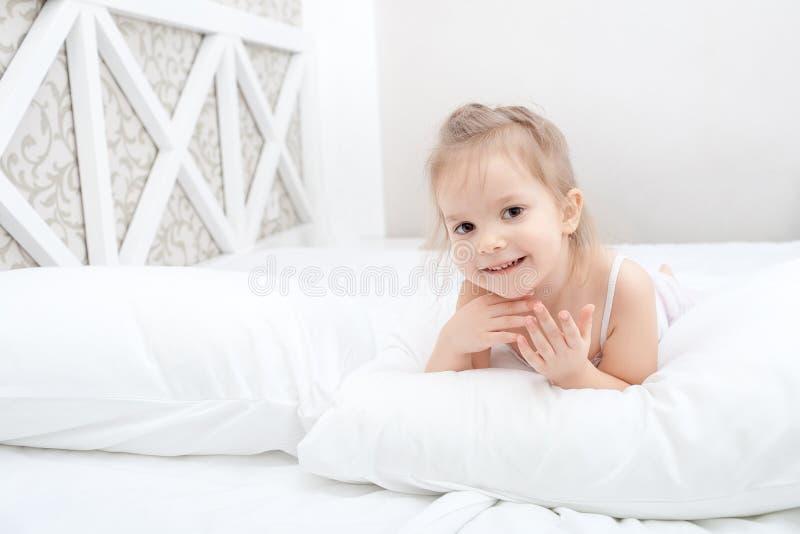 小孩女孩在软的床上 库存图片