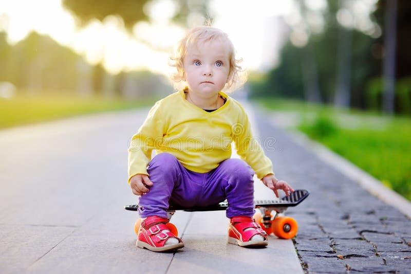 小孩女孩坐在夏天街道上的滑板 免版税库存照片