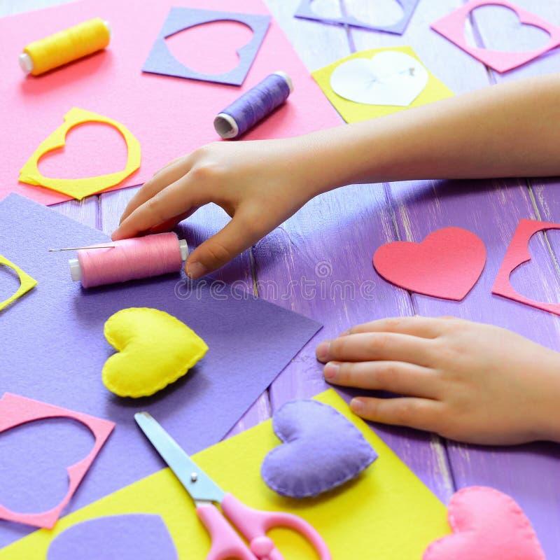小孩子做毛毡心脏 儿童在桌上的` s手 手工制造情人节心脏礼物、工艺材料和工具 库存图片