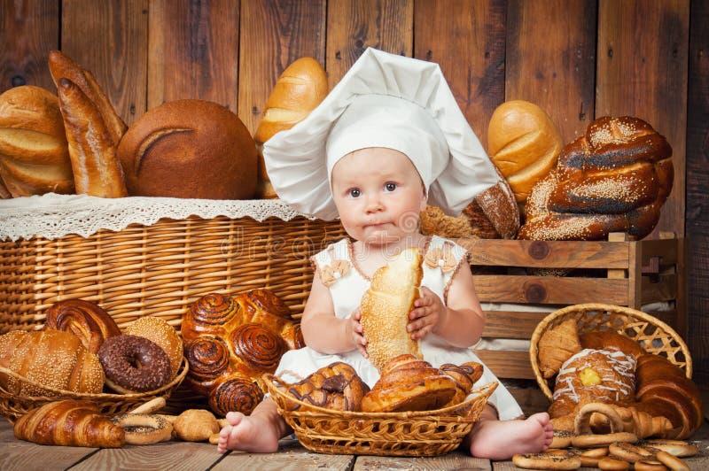 小孩子在篮子背景中烹调一个新月形面包与卷和面包的 图库摄影