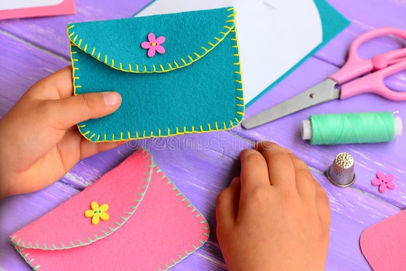 小孩子在他的手上拿着一个毛毡钱包 孩子显示一个毛毡钱包 手工造在一张木桌上的供应 图库摄影