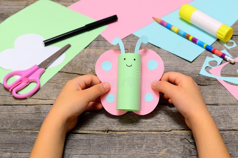 小孩子在他的手上的拿着纸蝴蝶 孩子显示纸工艺 滑稽的蝴蝶由色纸制成 库存照片