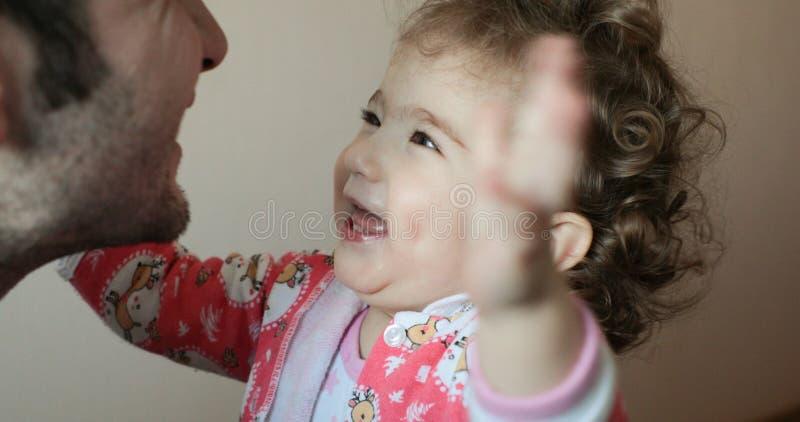 小孩子对一个人愉快地微笑并且画他的手给他 图库摄影