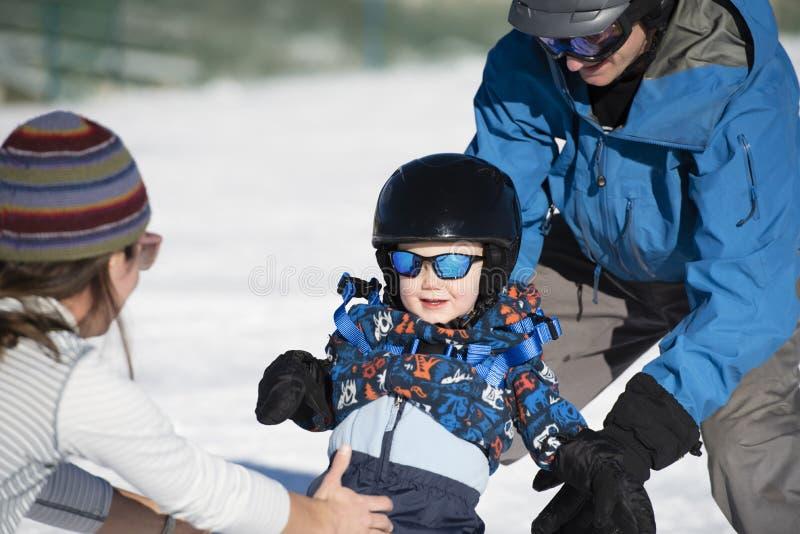 小孩学会滑雪与爸爸,当妈妈手表时 安全地穿戴 免版税库存图片