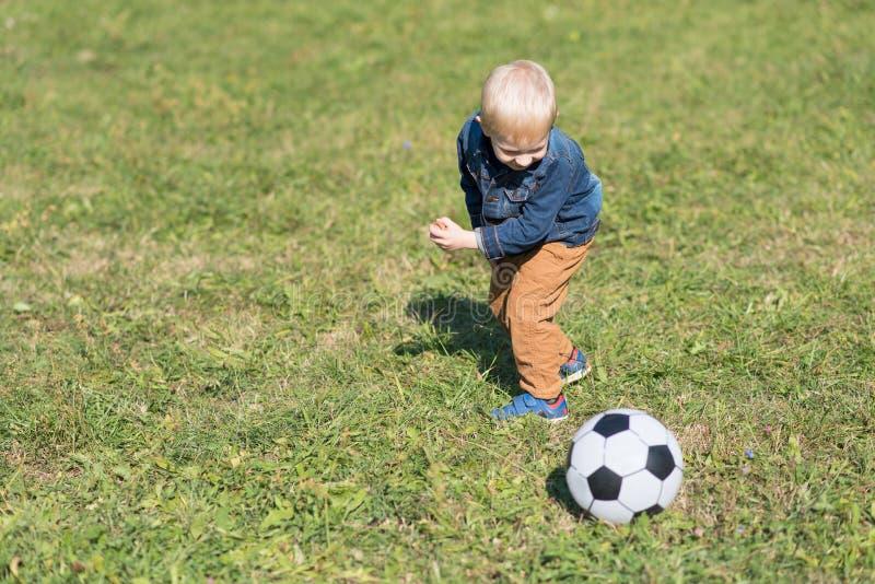小孩戏剧橄榄球在公园 库存图片