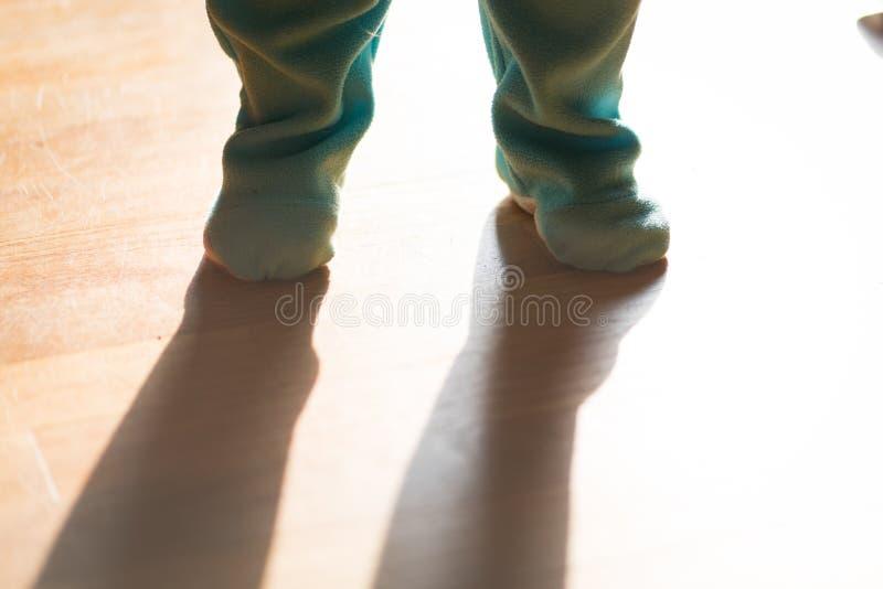 小孩或婴孩脚穿衣与剧烈的光 免版税库存照片