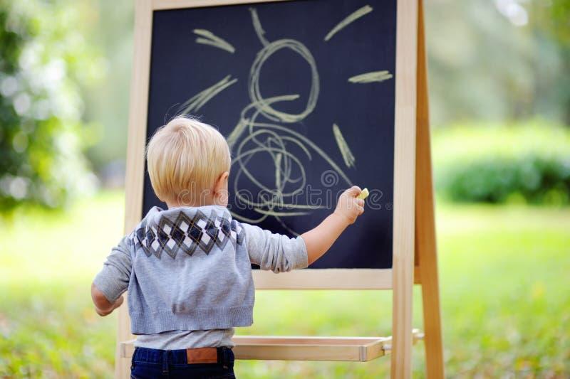 小孩支持黑板的男孩图画 图库摄影