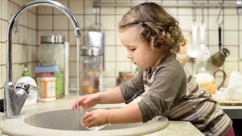 小孩是洗碗在厨房里 免版税图库摄影