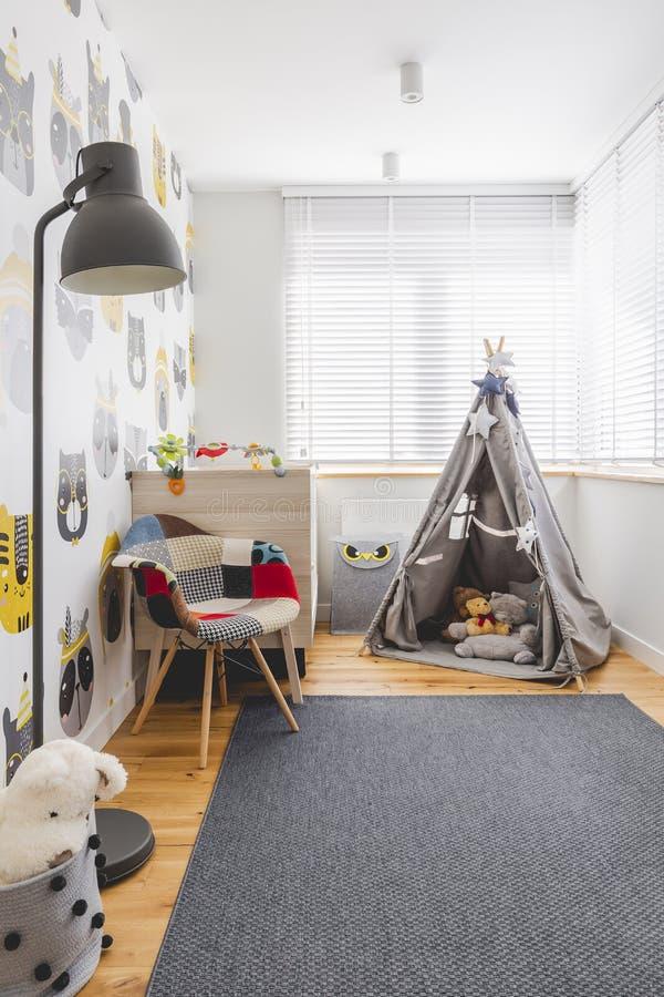 小孩游戏室的灰色帐篷、彩色扶手椅、灰色灯和地毯 免版税库存图片