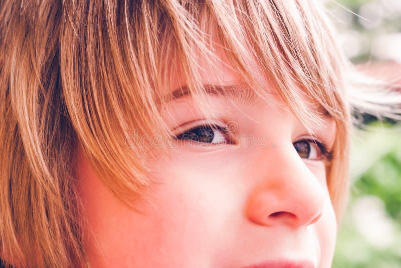 小孩狡猾的面孔表示室外知觉连接 免版税库存图片