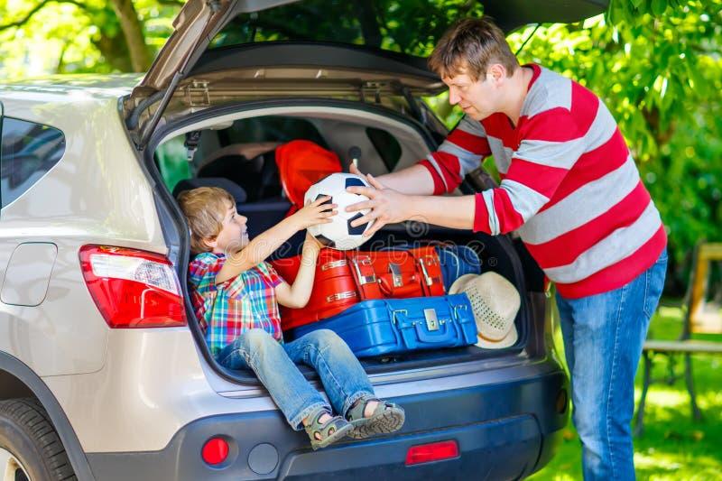 小孩男孩和父亲在离开前在汽车假期 免版税库存照片